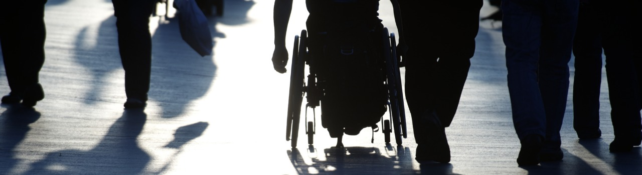 Following a man in a wheelchair surrounded by many people walking