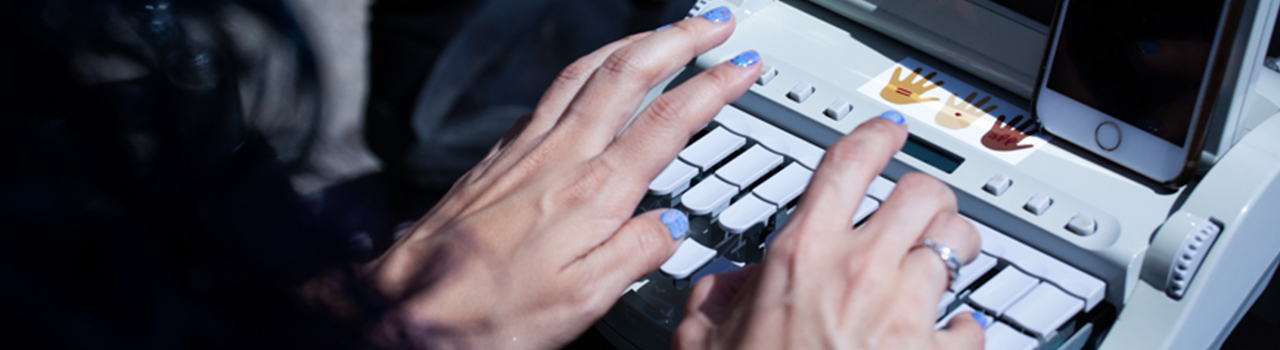 person with blue nail polish typing on a small machine with blank keys, and a small flip up screen with an iPhone resting against the screen