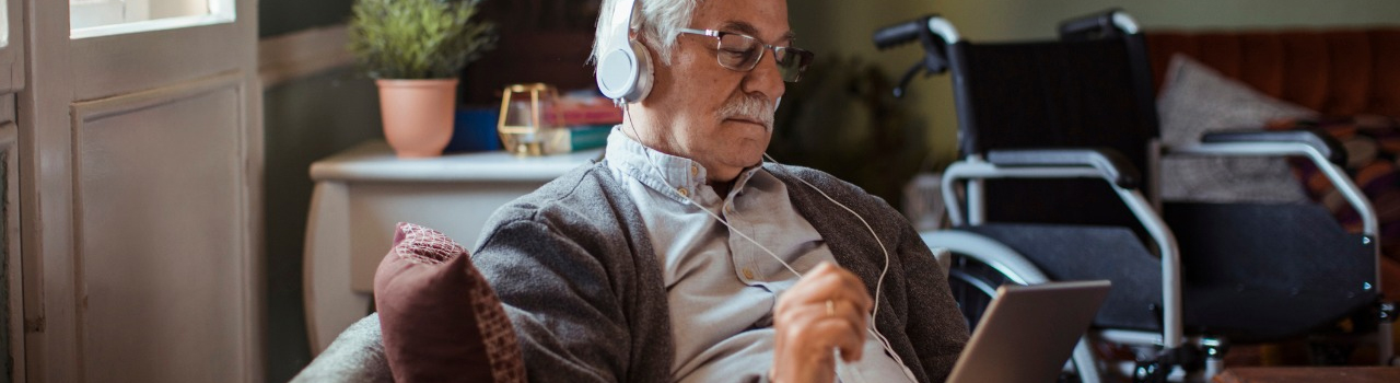 older gentleman in wheelchair wearing headphones connected to an ipad