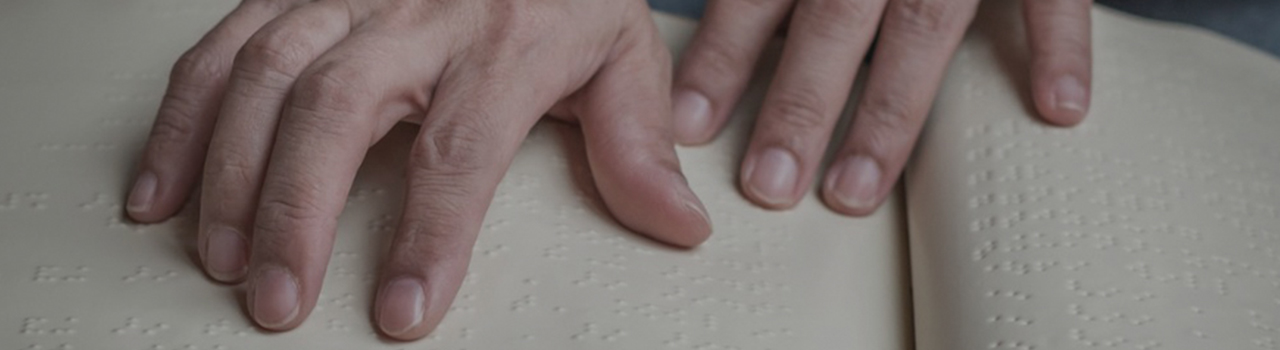two hands placed on an open book with pages that are covered in braille