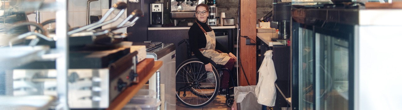 Woman in a wheelchair in a restaurant behind the counter looking at the camera down the working aisle