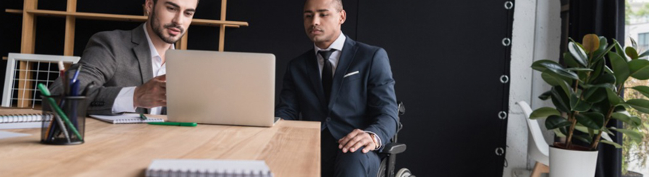 two multi-ethnic gentleman in business suits (one in a wheelchair) sitting behind a table looking at an open laptop computer