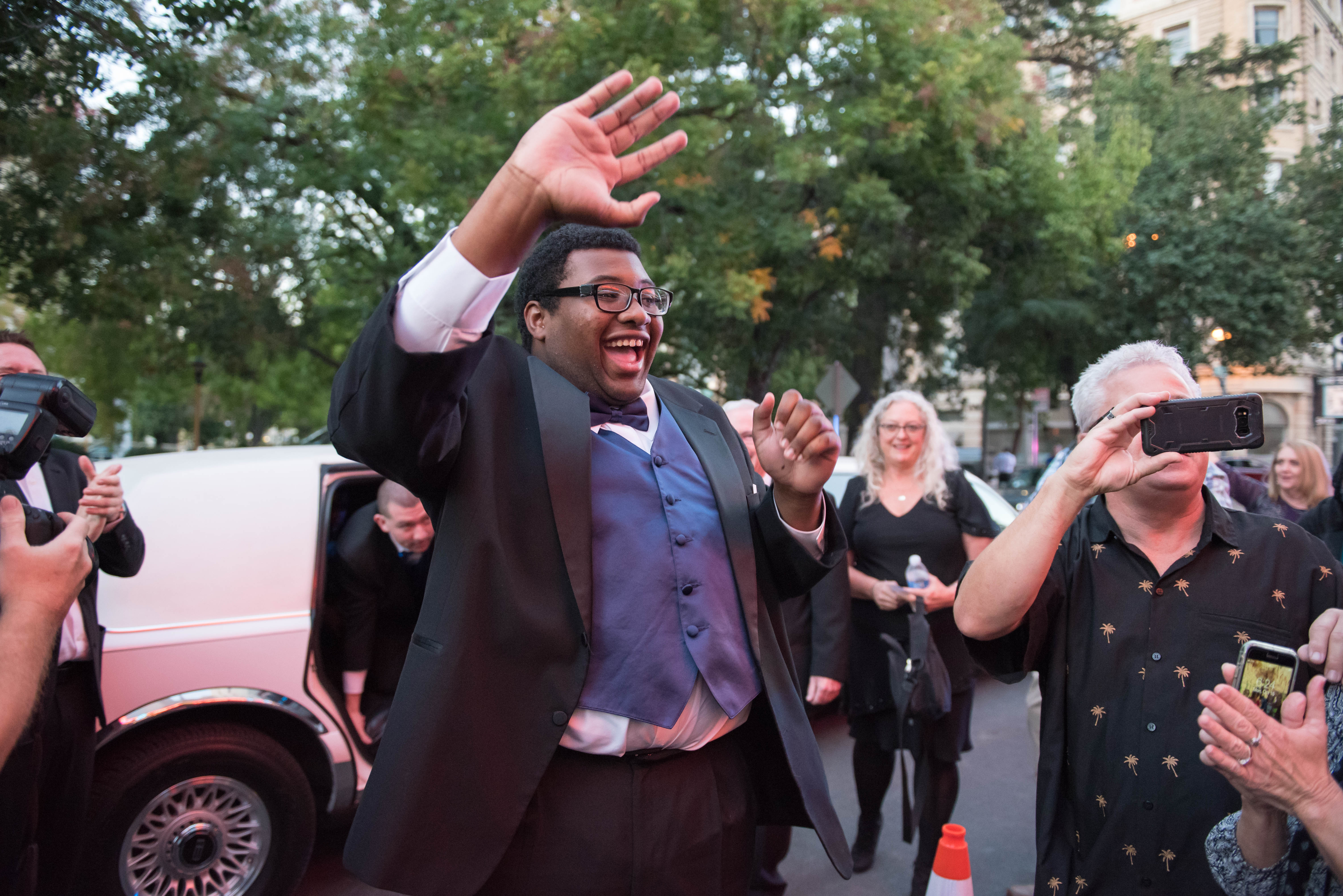 Young man wearing tuxedo steps out of limo on the red carpet smiling and waving